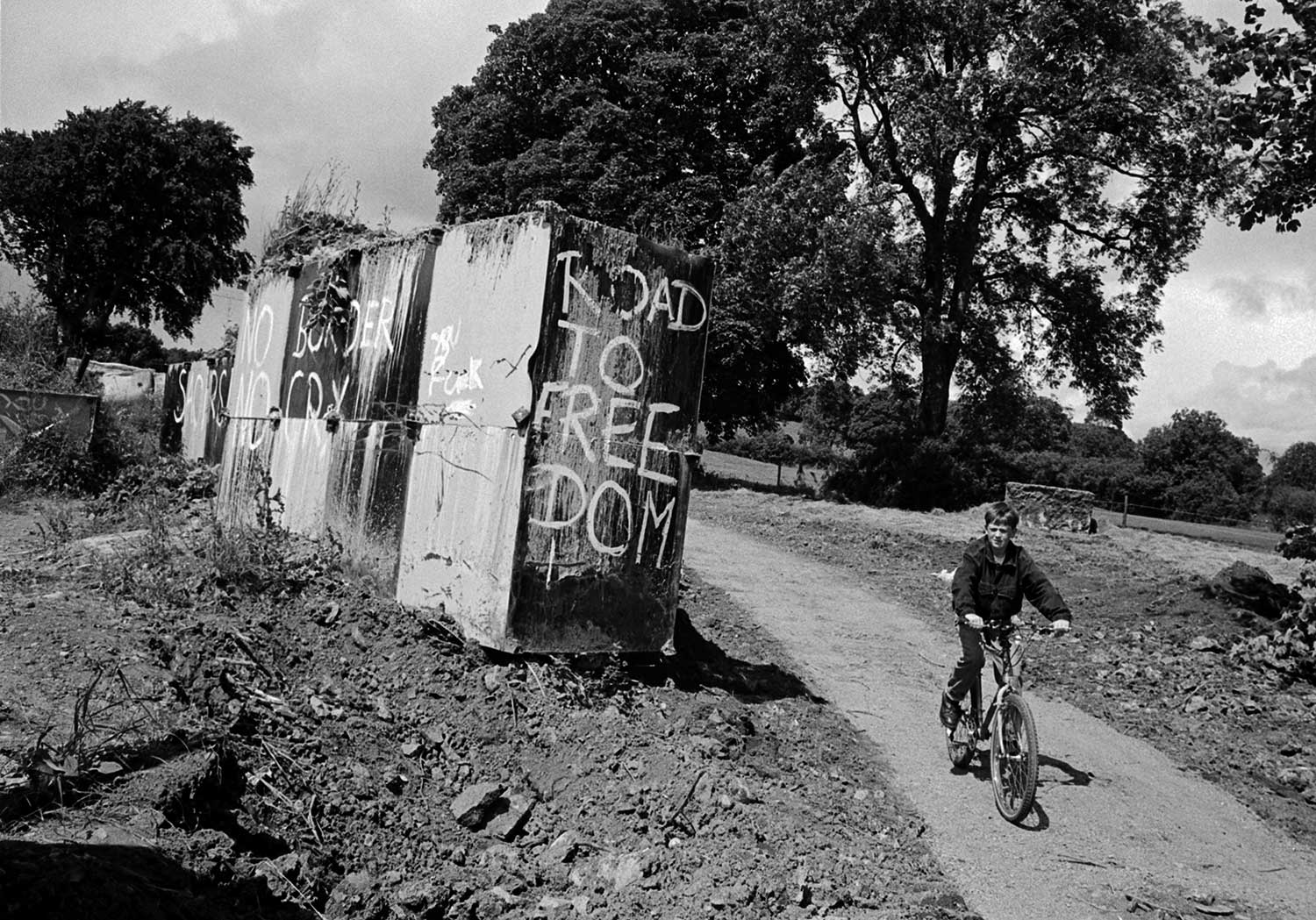 A young boy on his bike cycles on a dirt track past large concrete blocks painted with graffiti criticising the border