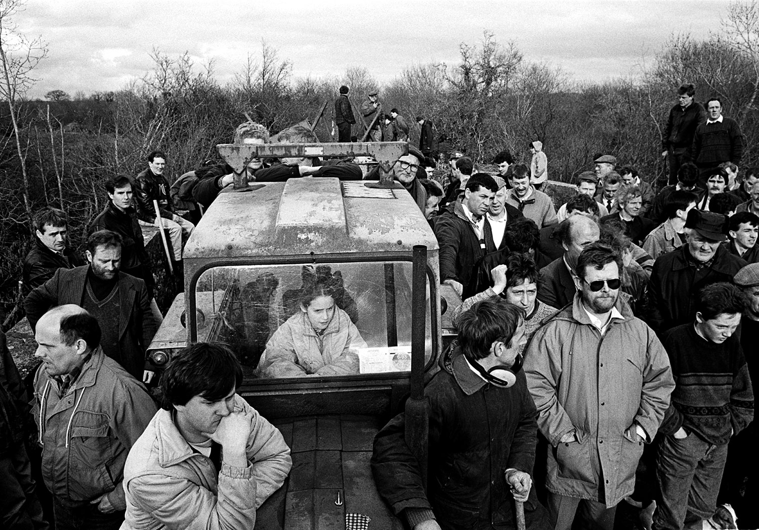 A crowd of men of all ages stand on a barricaded bridge looking at something off-screen. There is a lone girl sitting in a tractor in the middle of the crowd.