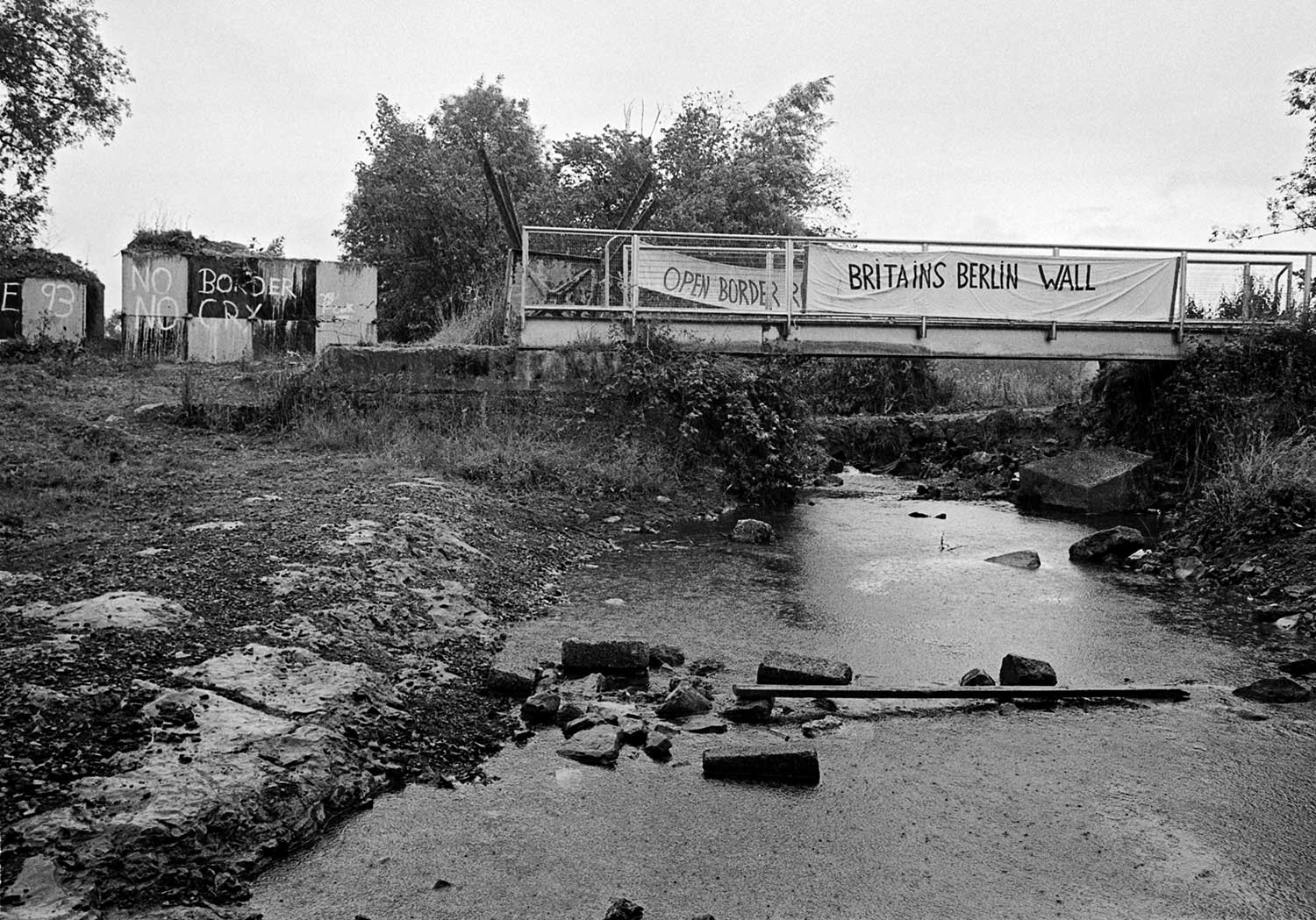 A small makeshift rusty bridge crosses a stream. Banners saying Britain's Berlin Wall and open border hang from the bridge.