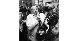 Edward I. Koch trying to play a bagpipe before the St. Patrick's Day parade on New York's Fifth Avenue, March 17th, 1983. Photograph: Fred R. Conrad/The New York Times