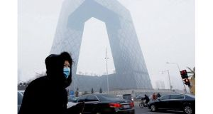 Foul fog: a woman walking past the CCTV building protects herself from the smog that covers a total area of 1.43 million sq km in Chinese cities. photographs: lintao zhang/getty; feng li/getty