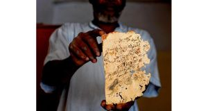 Konate Alpha holds an ancient manuscript he hid from extremists in Timbuktu;. Photograph: Tyler Hicks /New York Times