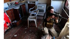 A fighter from the Sadik unit of Free Syrian Army's Tahrir al Sham brigade fires his rifle from inside a house during heavy fighting in Mleha suburb of Damascus. Photograph: Goran Tomasevic/Reuters