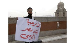 A man holds a sign in Arabic reading, '[Ahmedinejad] You are not welcome in Egypt