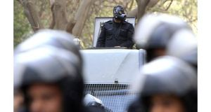 A policeman wears a gas mask in front of the Iranian Embassy as yrians living in Egypt protest against the visit of Iran's president Mahmoud Ahmadinejad to Cairo this week. Photograph: Mohamed Abd El Ghany/Reuters