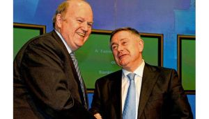 Minister for Finance Michael Noonan and Minister for Public Expenditure and Reform Brendan Howlin shake hands after yesterday's press conference on the bank debt deal. photograph: David Sleator/The Irish Times