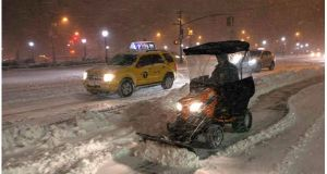 A snow plow blows snow in New York as a blizzard slammed into the northeastern part of the United States. Photograph: Keith Bedford/Reuters