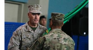 US general Joseph Dunford hands a flag to an unidentified US army personnel during a change-of-command ceremony at the Nato-led International Security Assistance Force (ISAF) headquarters in Kabul. Photograph: Omar Sobhani/Reuters