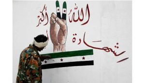 A member of the Free Syrian Army paints on the Al-Moshat school wall in Aleppo yesterday. The drawing reads 'God is great, martyrdom'. Photograph: Muzaffar Salman/Reuters