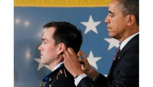 President Obama awards a Medal of Honor to Sergeant Clinton Romesha at the White House yesterday. Mr Obama is expected to announce the withdrawal of 34,000 troops from Afghanistan in his state of the union speech. Photograph: Jason Reed/Reuters