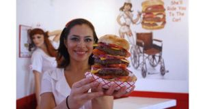A waitress at the calorie-friendly  Heart Attack Grill in Las Vegas shows off one of the burgers served at the restaurant. Photograph: Reuters