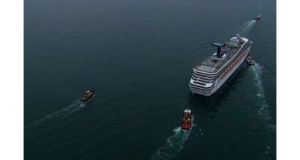 The cruise ship Carnival Triumph is towed in this video frame grab from NBC News taken off the coast of Alabama, 2013. Three tugboats were hauling the disabled  ship slowly into port in Mobile tonight where its arrival with more than 4,220 people ab