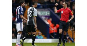 West Bromwich Albion's Goran Popov (left) is sent off by referee Mark Clattenburg after spitting at Kyle Walker (centre). Photograph: Darren Staples/Reuters