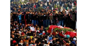 A crowd watches as the coffin of Chokri Belaid is carried during his funeral in the Jallez cemetery in Tunis yesterday. photograph: new york times