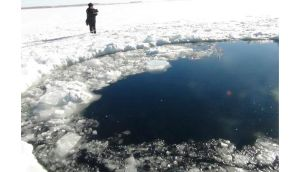 A Russian policeman works near an ice hole, said by the interior ministry department for Chelyabinsk region to be the point of impact of a meteor seen earlier in the Urals region. Photograph: Chelyabinsk region interior ministry/Reuters