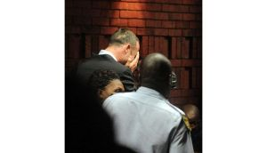 South African 'Blade Runner' Oscar Pistorius (left) is escorted by police at a Pretoria police station yesterday. Photograph: Reuters
