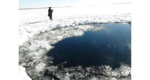 A Russian policeman works near an ice hole, said to be the point of impact of a meteor seen earlier in the Urals region, at lake Chebarkul yesterday. Photograph: Reuters