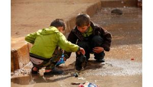 Children remove trash blocking the drains in the Al Inzarat district in Aleppo. Photograph: Reuters