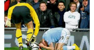 Craig Bellamy of Manchester City reacts after being hit by a coin thrown from the crowd at Old Trafford during the League Cup tie.