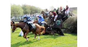 Horses and jockeys fall at Becher's Brook during yesterday's Grand National. There were two equine fatalities during the showpiece while jockey Peter Toole suffered serious head injuries in an earlier race. Photograph: John Giles/PA Wire.