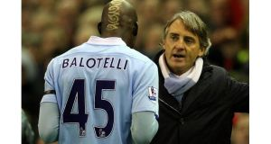 Manchester City manager Roberto Mancini speaks to Mario Balotelli as he heads for the dressing room after being sent off against Liverpool at Anfield today. – (Photograph: Alex Livesey/Getty Images).