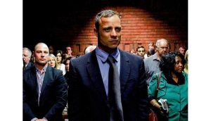 Oscar Pistorius awaits the start of court proceedings while his brother Carl (left) looks on. photograph: siphiwe sibeko/reuters