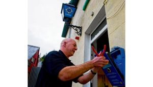 A Garda technician removes the 'blue man' or public access call box from Ashford Garda Station in Co Wicklow. All rural Garda stations are to have these removed in the coming months. photograph: garry oneill