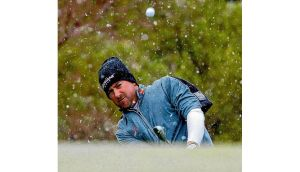 Graeme McDowell hits to the first green as snow falls in the desert during the first round of the WGC-Accenture Match Play Championship in Arizona yesterday