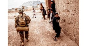 War games: an Afghan boy mimes shooting US soldiers as they patrol his village, in Kandahar province, this year. photographs: bryan denton/new york times, pa