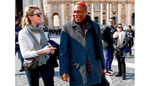 Cardinal John Olorunfemi Onaiyekan of Nigeria talks to a tourist in St Peter's Square in Rome yesterday. Preparations for electing a new pope began in earnest yesterday as the college of cardinals opened daily talks. photograph: reuters