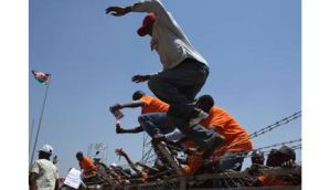 Orange Democratic Movement supporters jump a security fence to get party T-shirts during the last campaign rally at the Nyayo National Stadium in Nairobi yesterday ahead of the presidential election tomorrow. Photograph: Siegfried Modola/Reuters