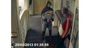 A man dressed as Batman walked into a police station and handed over a wanted man to officers.