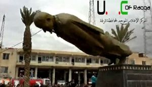 A statue of President Bashar Al-Assad's father, Hafez Al-Assad, is pulled down as people celebrate in Raqqa last night. Image: Reuters