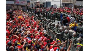 Supporters of deceased Venezuelan leader Hugo Chavez gather to watch as his coffin is driven through the streets of Caracas. Photograph: Carlos Garcia Rawlins/Reuters