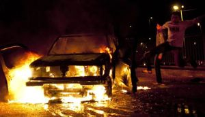 An Egyptian protester kicks a police pickup truck that was set on fire by anti-president Mohammed Morsi protesters in Cairo, Egypt.