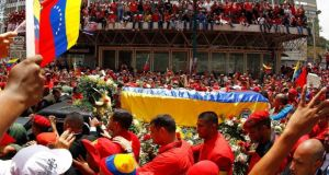 The coffin of deceased Venezuelan leader Hugo Chávez is driven through the streets of Caracas. Photograph: Carlos Carcia/Reuters