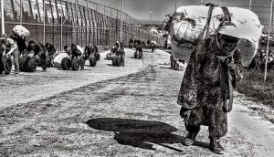 One of the women walking towards the Melilla-Morocco border with a heavy pack on her back, while a group of men push tires. photographs: fernando molina