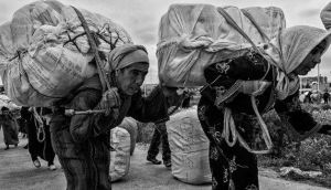 Two women walk towards the border with heavy loads on their backs. photographs: fernando molina