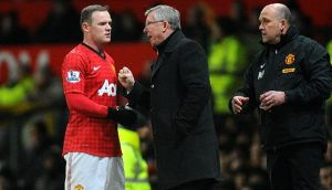 Manchester United manager Alex Ferguson (centre) speaks with Wayne Rooney on the touchline. Photograph: Martin Rickett/PA