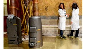 Workers stand next to stoves in the Sistine Chapel. photograph: reuters