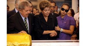 Brazil's former President Luiz Inacio Lula da Silva (left), Brazil's President Dilma Rousseff and Rosa Virginia, daughter of Venezuela's late president Hugo Chavez, view his coffin during a wake in Caracas yesterday. Photograph: Reuters