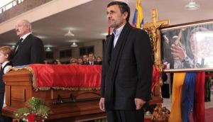 Iran's president Mahmoud Ahmadinejad standing next to the coffin of Hugo Chávez.