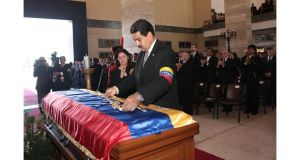 Venezuelan vice-president Nicolas Maduro lays a replica of the Simon Bolivar's sword on the coffin of Venezuela's late President Hugo Chavez at the Military Academy in Caracas. Photograph:  Miraflores Palace/Handout/Reuters