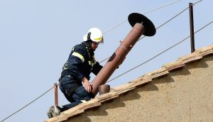A member of the fire and rescue service sets a chimney on the roof of the Sistine Chapel at the Vatican Photograph: Dylan Martinez/REUTERS