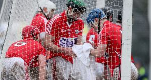 Cork players dry their hands and hurls before defending a free. Photograph: James Crombie/Inpho