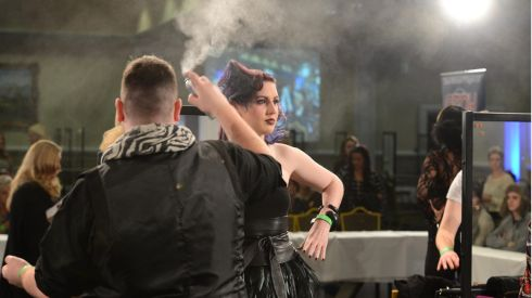 Lights, camera, hairspray...hairdresser Aaron Healy with model Darina Lynch during the senior ladies fashionable hairstyle on long hair event at the IHF National Hairdressing Championships 2013. Photograph: Dara Mac Dónaill/The Irish Times   Photographer: Dara Mac D?naill / THE IRISH TIMES             Photographer: Dara Mac Donaill / THE IRISH TIMES