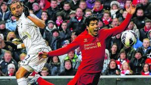 Luis Suarez (R) is challenged by  Benoit Assou-Ekotto to concede  a penalty  at Anfield. Photograph: Phil Noble/Reuters