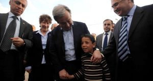 United Nations High Commissioner for Refugees (UNHCR) Antonio Guterres (C) walks with a Syrian refugee boy during his visit at a refugee camp in Nizip in Turkey's southern Gaziantep province, yesterday. The number of refugees outside Syria could triple by the end of the year if there is no political solution to the conflict, the head of the UN refugee agency said. Photograph Veli Gurgah/Reuters