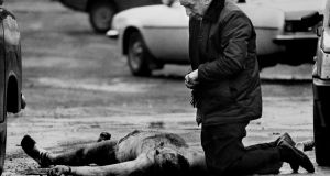 Fr Alex Reid gives the last rites to corporal David Howes, one of two British army soldiers who were killed in West Belfast on the 19th March 19th, 1988.   Photograph: Trevor McBride