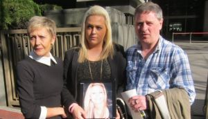 Andrea Furlong holds a photograph of her sister Nicola outside Tokyo District Court with her father Andrew and mother Angela today.